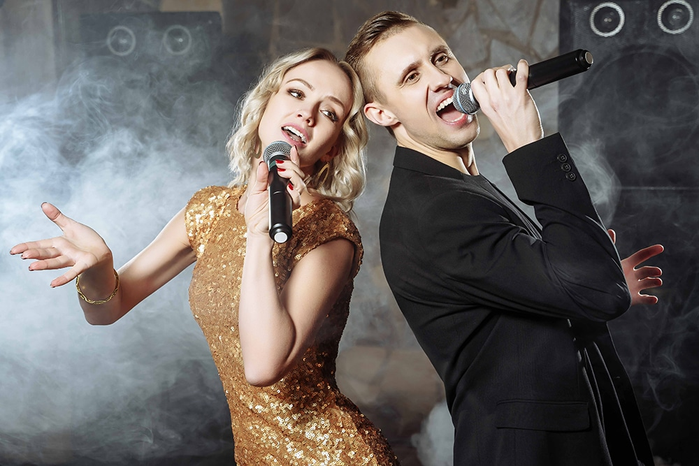 Portrait of a young couple singing into a microphone in a club.